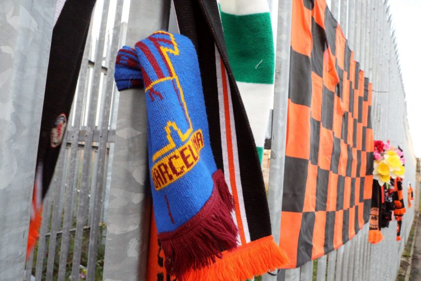 Scarves and other items left by fans at Tannadice yesterday.