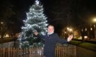 Colin Clement, chair of the Stobswell Community Forum switches on the Christmas tree lights.