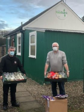 irefighter Kenny Petrie from Kirriemuir Fire Station with Angus Foodbank Manger Norman Brown.