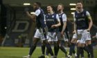 Dundee players celebrate their third goal against Hearts.