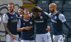 Jonathan Afolabi (second right) is mobbed by Dundee team-mates.