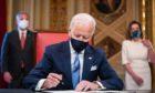 US President Joe Biden signs three documents.
