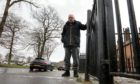 Jim Elder, 81, hangs on to the railings outside is home in Lundie Avenue in Dundee