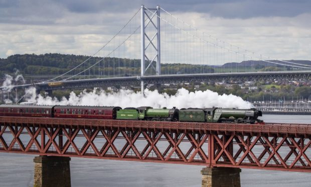A Victorian train, The Flying Scotsman, travels on a Victorian span, the Forth Bridge, in 2020.