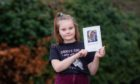 Summer Gray (aged 8) holding her dad's picture from the order of service.