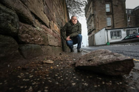 Councillor Charlie Malone at Burnside Street beside the decaying stone wall with the block that fell from it (Picture: Mhairi Edwards/DCT Media)
