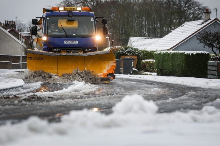 S snow plough drives though Monikie to clear the roads last week.