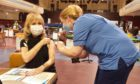 Margaret Scott receiving her vaccination at the Caird Hall from vaccinator Suzy Black