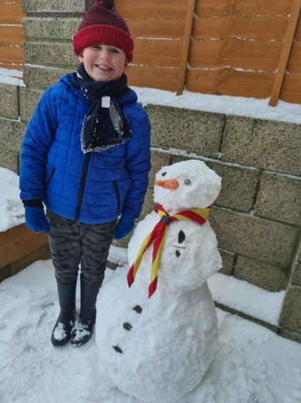 Cameron 8, from Dundee, with his cub scout snowman who has his own membership badge.
