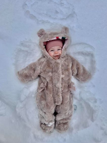 Lily Hutchison, 19 weeks old, making snow angels for her first time in the snow in Dundee.