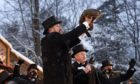 Groundhog Club handler A.J. Dereume holds Punxsutawney Phil, the weather prognosticating groundhog, on Tuesday.