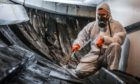 Technician Stuart Dalzell sprays the ship  to help preserve her.