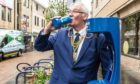 Fife Provost Jim Leishman tries out a top up tap in Dunfermline.