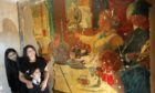 Asia Akram with her daughters Ayaana, six, and Myesha, 13, with the mural uncovered in their home.
