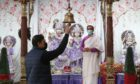 Assistant priest Deepak Shastri watches as worshiper Sudhir Jaidke rings the bell at the Hindu Mandir Glasgow after the partial easing of lockdown restrictions in Scotland allowing communal worship to resume. Picture date: Friday March 26, 2021. PA Photo. See PA story SCOTLAND Coronavirus. Photo credit should read: Andrew Milligan/PA Wire