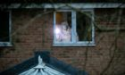 Forensics officers examining a bedroom in the Troon Avenue property on Saturday evening.