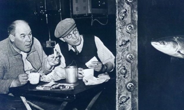 This picture, taken in the 1950s, shows Sandy Philips, left, enjoying his lunch with a colleague in the observation chamber while being spied on by a salmon making its way up the ladder