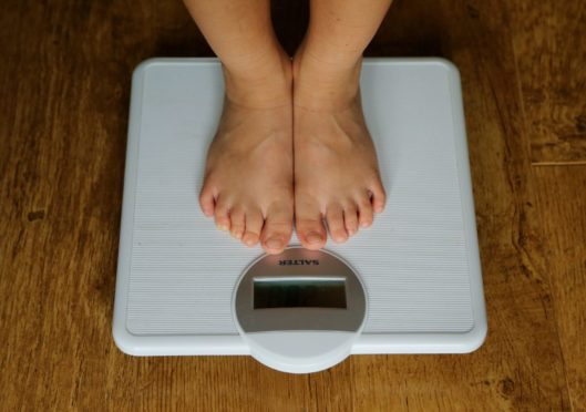 Feet on a set of scales measuring a persons weight