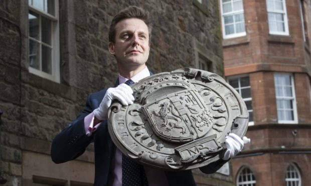 Head of House Sales Charlie Thomson holds one of four carved oak armorial panels from The Queen Regent's House, Blythe's Close, Edinburgh, which shows the impaled arms of King James V of Scotland and Mary Guise (the parents of Mary Queen of Scots). The armorial panels sold at auction for £17,750 at the Bonhams Edinburgh Dunrobin Attic Sale, an auction of hundreds of items found in the attics and cellars at Dunrobin Castle in Sutherland, the family seat of the 25th Earl of Sutherland. Picture date: Wednesday April 21, 2021. PA Photo. See PA story SALE Castle. Photo credit should read: Jane Barlow/PA Wire