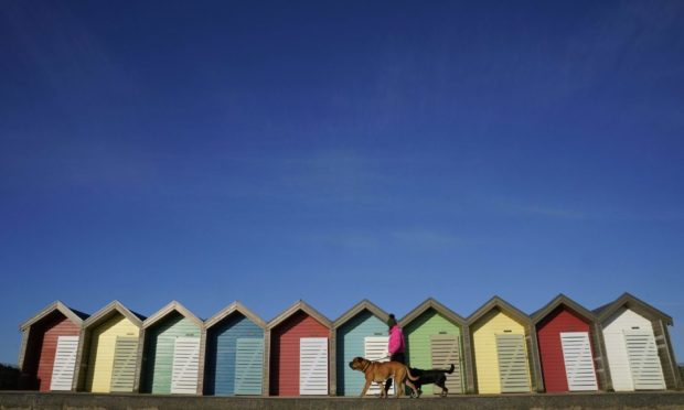 A woman walks her dog past beach huts at Blyth beach in Northumberland in the cold. Picture date: Wednesday April 7, 2021. PA Photo. Photo credit should read: Owen Humphreys/PA Wire