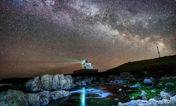 The core of the Milky Way becomes visible in the early hours of Tuesday morning as it moves over Bamburgh Lighthouse at stag Rock in Northumberland. Picture date: Tuesday April 13, 2021. PA Photo. Photo credit should read: Owen Humphreys/PA Wire