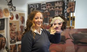 Topaz Walker, 17, with the mask she made depicting her grandpa Jim.