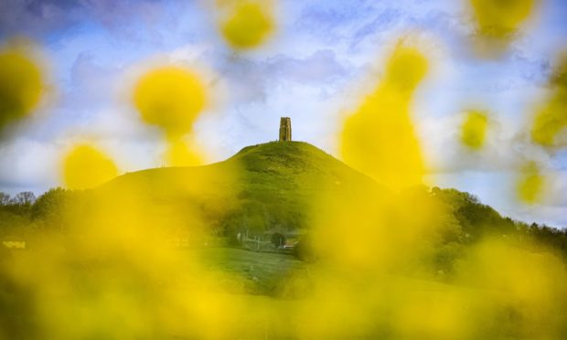 People mill around St. Michael's tower on top of Glastonbury Tor as it is seen through blooming yellow rapeseed on a day of mixed weather in Glastonbury, Somerset. Picture date: Sunday May 9, 2021. PA Photo. Photo credit should read: Ben Birchall/PA Wire
