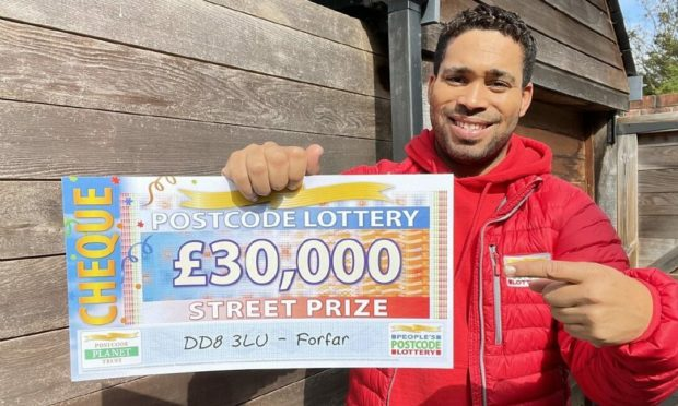 People's Postcode Lottery ambassador Danyl Johnson with a cheque for £30,000.