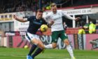 Dundee's Lee Ashcroft (left) competes with Hibernian's James Scott.