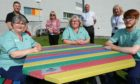 Back, L-R: Richard McIntosh (NHS), Jenny Alexander (NHS employee director), Gary Preston (production officer NHS Tayside), Trudy McLeay (non-executive director with NHS Tayside health board). Front: Laundry staff Jane Livingston, Yvonne Scott and Ciaran Fraser at the outdoor seating.