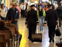 Two British Airways Pilots walking through departures of Terminal 5 at Heathrow Airport (Steve Parsons/PA)