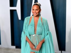Chrissy Teigen has revealed she is torn about undergoing further breast surgery due to fears of complications on the operating table (Ian West/PA)