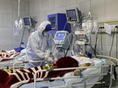 A medic treats a patient infected with coronavirus, at a hospital in Tehran (AP)