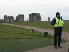 A security guard near Stonehenge in Wiltshire, where the traditional equinox celebrations inside the stones were cancelled (Adam Davy/PA)