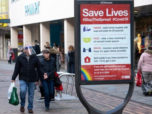 A man wearing a face shield walks past a coronavirus advice sign in Nottingham city centre (Jacob King/PA)