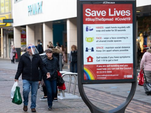 A man wearing a face shield walks past a coronavirus advice sign in Nottingham city centre (PA)