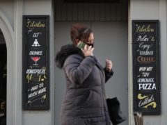 A woman passes a closed pub in Hamilton, where Level 4 restrictions could be introduced (Andrew Milligan/PA)
