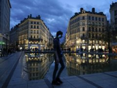 A man wearing a mask walks in the street in the centre of Lyon, central France (Laurent Cipriani/AP)