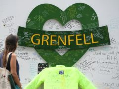 People at the Grenfell Memorial Community Mosaic at the base of the tower block (Kirsty O'Connor/PA)