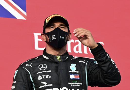 Lewis Hamilton celebrates on the podium after winning the Emilia Romagna Grand Prix (Miguel Medina, Pool via AP)