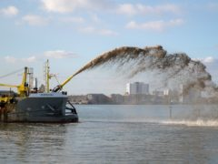 The dredger Sospan Dau sprays gravel on to the foreshore at Portsmouth to develop a temporary working platform during the first stages of a £100m sea defence scheme (Andrew Matthews/PA)