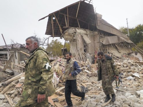 Ethnic Armenian soldiers walk past a house destroyed by shelling by Azerbaijan's artillery in Stepanakert, the separatist region of Nagorno-Karabakh, Friday, Nov. 6, 2020. Nagorno-Karabakh authorities said that three civilians were killed by Azerbaijani shelling of the regional capital, Stepanakert on Friday. (AP Photo)