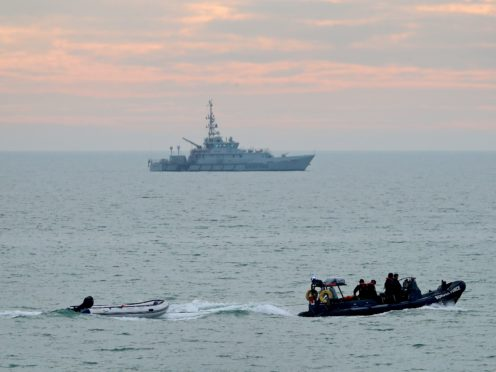 A small boat is towed by a Border Force vessel in the English Channel (Gareth Fuller/PA)
