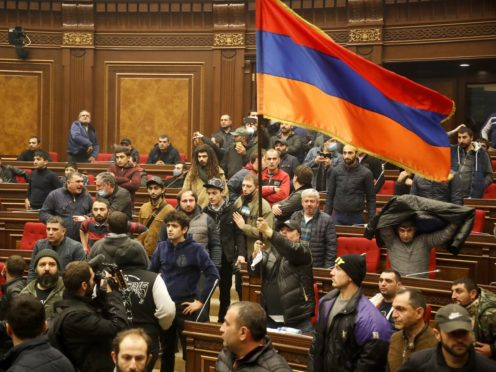 Demonstrators with an Armenian national flag protest against an agreement to halt fighting over the Nagorno-Karabakh region, at the parliamentary building in Yerevan, Armenia, on Tuesday (Dmitri Lovetsky/AP)