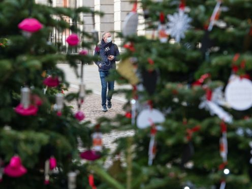 A man wearing a face mask is seen among Christmas trees in London (Dominic Lipinski/PA)