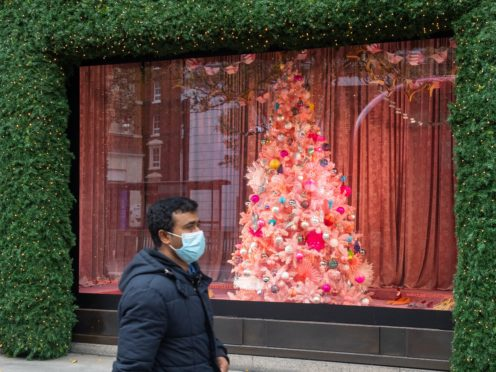 A shopper wearing a face mask passes a Christmas window display on Oxford Street, London (PA)