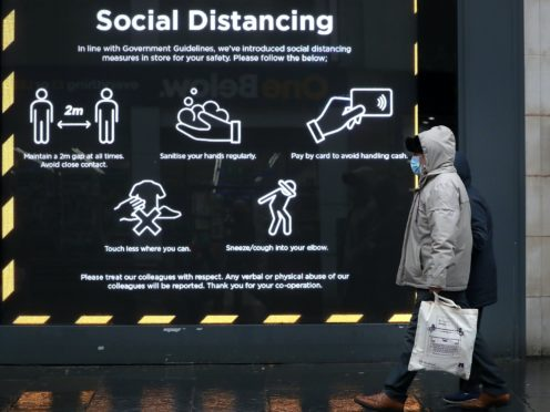 A member of the public walks passed a social distancing sign in a shop window in Glasgow (Andrew Milligan/PA)