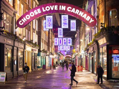 People walk under Christmas lights on Carnaby Street in central London (Dominic Lipinski/PA)