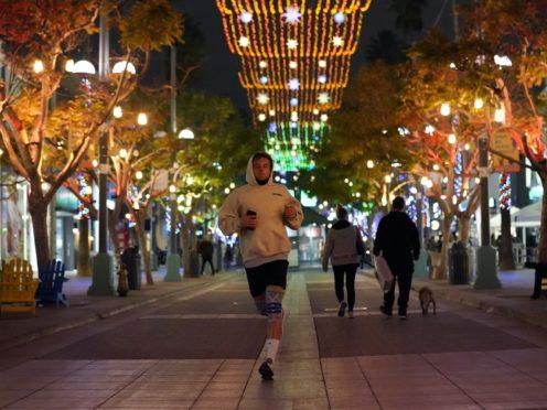 A jogger runs through a shopping district in Santa Monica, California (Marcio Jose Sanchez/AP)