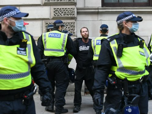 A man is detained by police during an anti-lockdown protest in Whitehall, London (Stefan Rousseau/PA)